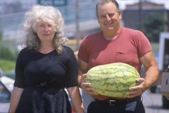 Man and woman walking with watermelon Royalty Free Stock Image