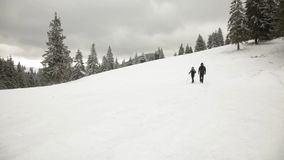 Man and Woman walking in winter mountains stock footage
