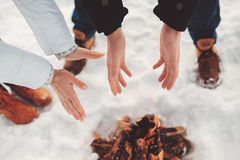 Man and woman warm their hands near fire Stock Images
