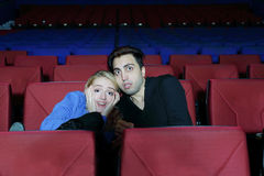 Man and woman watch movie and press close to one another in fright Royalty Free Stock Photos