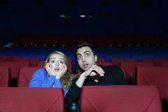 Man and woman watch movie and very much afraid in movie theater. Royalty Free Stock Photo