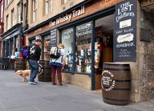 Curiosity of passersby. A man and a woman are watching an alcohol store`s site in Edinburgh royalty free stock photo