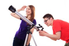 Man and woman watching the stars through a telescope Royalty Free Stock Image