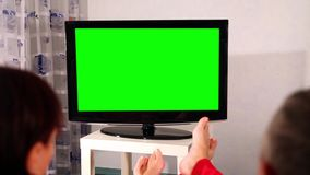 Man and woman watching television. Green screen.