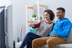 Man and woman watching tv on couch Royalty Free Stock Image