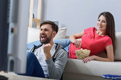Man and woman watching tv on couch Stock Image