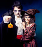 Man and woman wearing as vampire and witch. Carnival. fog. Royalty Free Stock Image