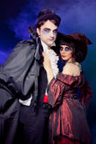 Man and woman wearing as vampire and witch. Carnival. fog. Royalty Free Stock Photography