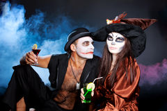 Man and woman wearing as vampire and witch. Halloween. Man and women wearing as joker and witch. Hallowee royalty free stock photos