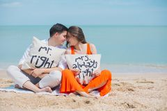 Man and Woman Wearing Cloths Sitting on Brown Sand Near Seashore Stock Images