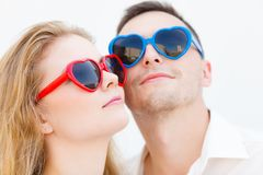 Man and woman wearing heart shape sunglasses Royalty Free Stock Image