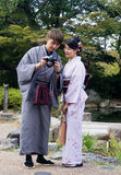 Man and woman wearing kimono taking pictures. Kyoto, Japan - September 30, 2015: Young couple dressed in beautiful kimono looking at pictures on camera in Stock Image