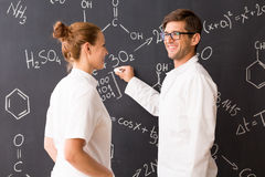 Man and woman wearing labcoats standing in front of a blackboard Royalty Free Stock Photos