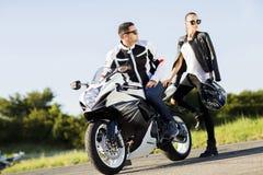 Man and woman wearing leather jackets and stylish sunglasses rid Stock Photo