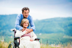 Man with woman in wheelchair Stock Photos