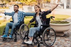 A man and a woman on wheelchairs ride around the park. They put their hands to one side and fooled around. A men and a women on wheelchairs ride around the park Stock Photos