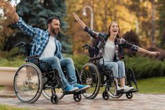 A man and a woman on wheelchairs ride around the park. They put their hands to one side and fooled around. A men and a women on wheelchairs ride around the park Stock Image