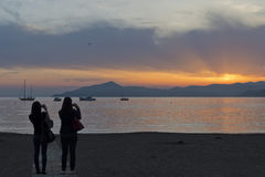 Man and woman whiile kissing on sestri levante beach at sunset Royalty Free Stock Photos