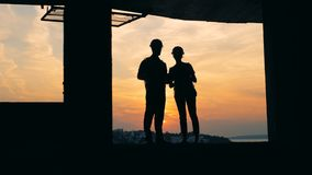 Man and woman work in a building on a sunset background, close up. stock video footage