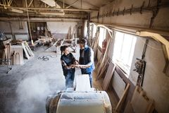 Man and woman workers in the carpentry workshop holding wood. Royalty Free Stock Photo