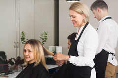 Man and woman working in the barbershop. Man and women working at the barbershop stock photo