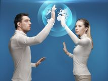 Man and woman working with globe hologram Stock Photography