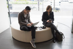 Man and woman working on laptop and mobile phone. Man and women sitting on round sofa couch working on laptop and mobile phone royalty free stock photos