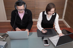 Man and woman working on laptops. Man and women surrounded by technology, working on laptops, with tablets and phones stock image