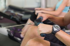 Man and woman working out on the rowing machine Stock Images