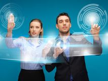 Man and woman working with virtual touch screens Royalty Free Stock Photography