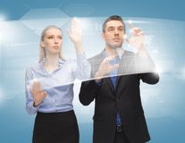 Man and woman working with virtual touch screens. Picture of men and women working with virtual touch screens Royalty Free Stock Images