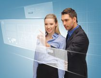 Man and woman working with virtual touch screens Stock Images