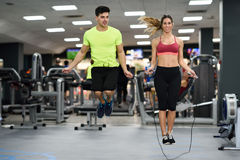 Man and woman workout with jumping rope in crossfit gym. Handsome men and beautiful sporty women workout with jumping rope in crossfit gym Stock Images