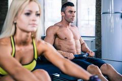 Man and woman workout on training simulator Stock Photos