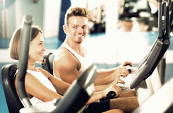 Man and woman workout using cycling cardio machines Stock Photos