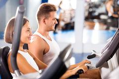 Man and woman workout using cycling cardio machines Royalty Free Stock Images