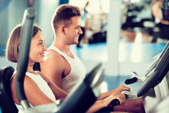 Man and woman workout using cycling cardio machines Stock Images