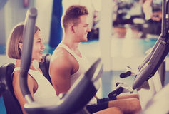 Man and woman workout using cycling cardio machines. Portrait young glad men and beautiful women warming up before workout using cycling cardio machines Stock Photography