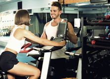 Man and woman workout using cycling cardio machines Royalty Free Stock Photos