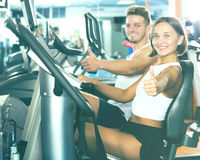 Man and woman workout using cycling cardio machines. Young glad men and pretty women warming up before workout using cycling cardio machines Stock Images