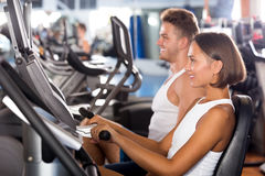 Man and woman workout using cycling cardio machines Royalty Free Stock Photo