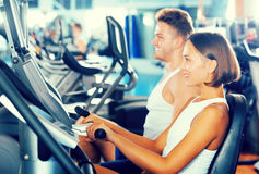 Man and woman workout using cycling cardio machines. Young glad men and women warming up before workout using cycling cardio machines Stock Image
