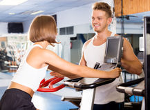 Man and woman workout using cycling cardio machines. Young handsome men and women warming up before workout using cycling cardio machines Royalty Free Stock Photos