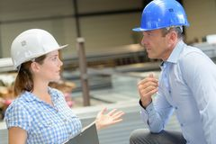 Man and woman in workplace wearing hardhats Stock Photos