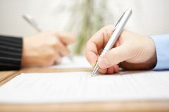 Man and woman writing on document Royalty Free Stock Images