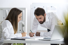 Man and woman writing and talking Stock Image