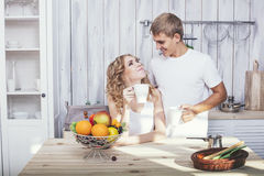 Man and woman young and beautiful couple in the kitchen home coo Royalty Free Stock Images