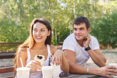 Man and woman or young couple drinking coffee in city park Royalty Free Stock Image