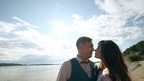 Man and woman, young happy married couple silhoutte kissing on the shore. stock footage