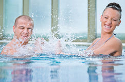Man woman young splashing swimming pool Stock Photography